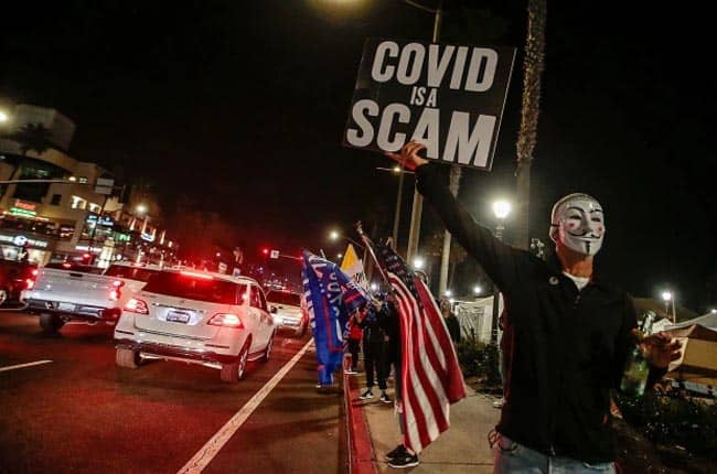 A Huntington Beach protester holds Covid is a scam sign. Credit: Rex Features